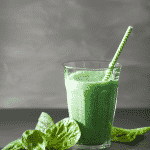 Cup of green smoothie with fresh spinach on the side.