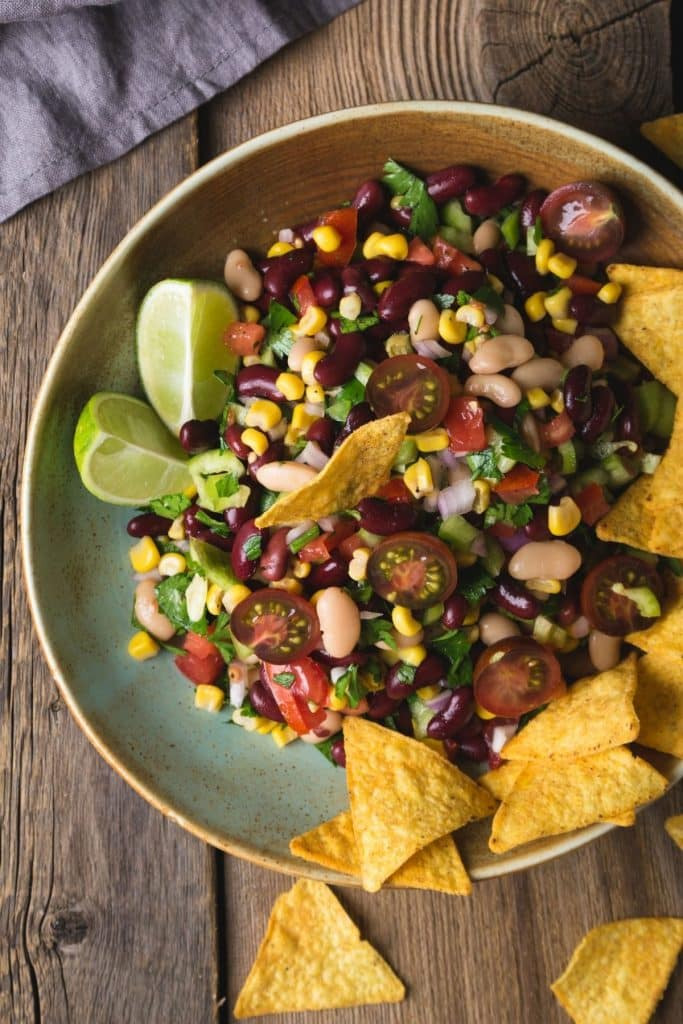 Bowl of bean salad with lime wedges and tortilla chips.