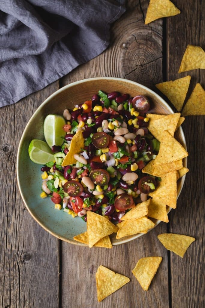 Bowl of Texas Caviar with lime wedges and tortilla chips.