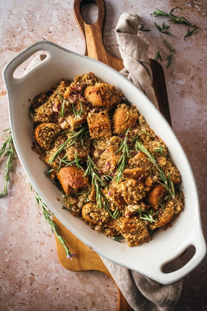 Stuffing served in an oval ceramic baking dish with fresh rosemary on top.