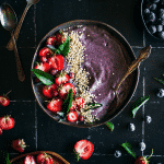 Blueberry smoothie topped with strawberries, pink blueberries, popped quinoa, on a black tile background surrounded by strawberries and blueberries.