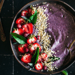 Up close blueberry smoothie bowl made with bananas, acai, and almond butter.