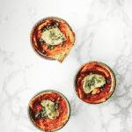 Four vegan lasagnas in green enamel cups.