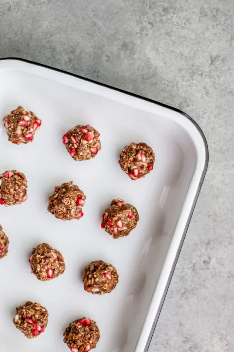 Pomegranate oat balls on a black rimmed white enamel tray.