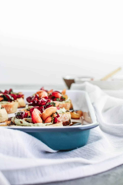 Cherry bruschetta with a balsamic glaze on a white enamel tray and white cloth napkins
