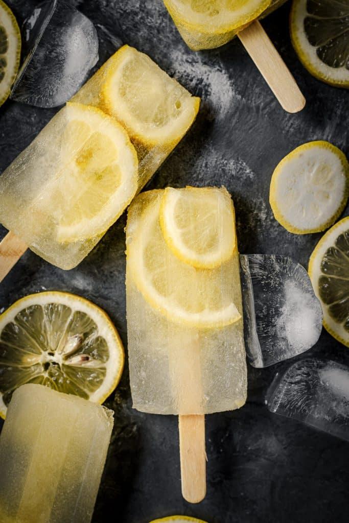Close up of lemon popsicles with fresh slices of lemon.