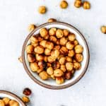 Bowl of cheesy roasted chickpeas on a gray background.