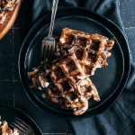 Triangle shaped potato waffles on black plates.