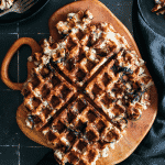 Large potato waffle on a wooden board.