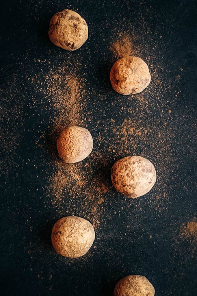Chocolate date balls on a slate surface.