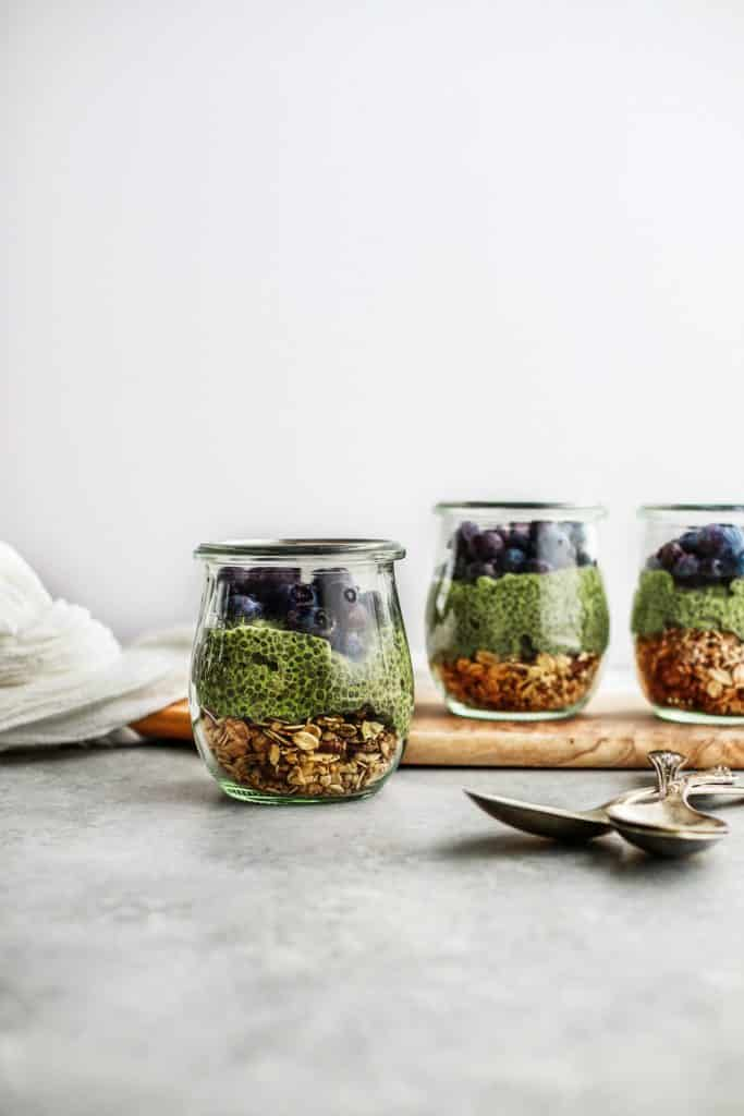 Layered jar of granola, green chia pudding, blueberries, and chocolate.