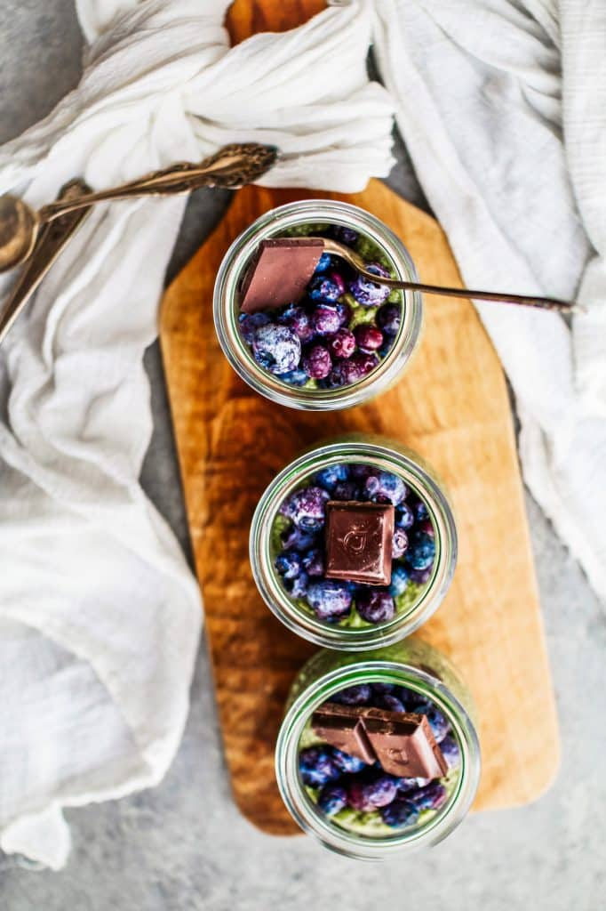 Jars of matcha chia seed pudding topped with blueberries and a piece of chocolate.