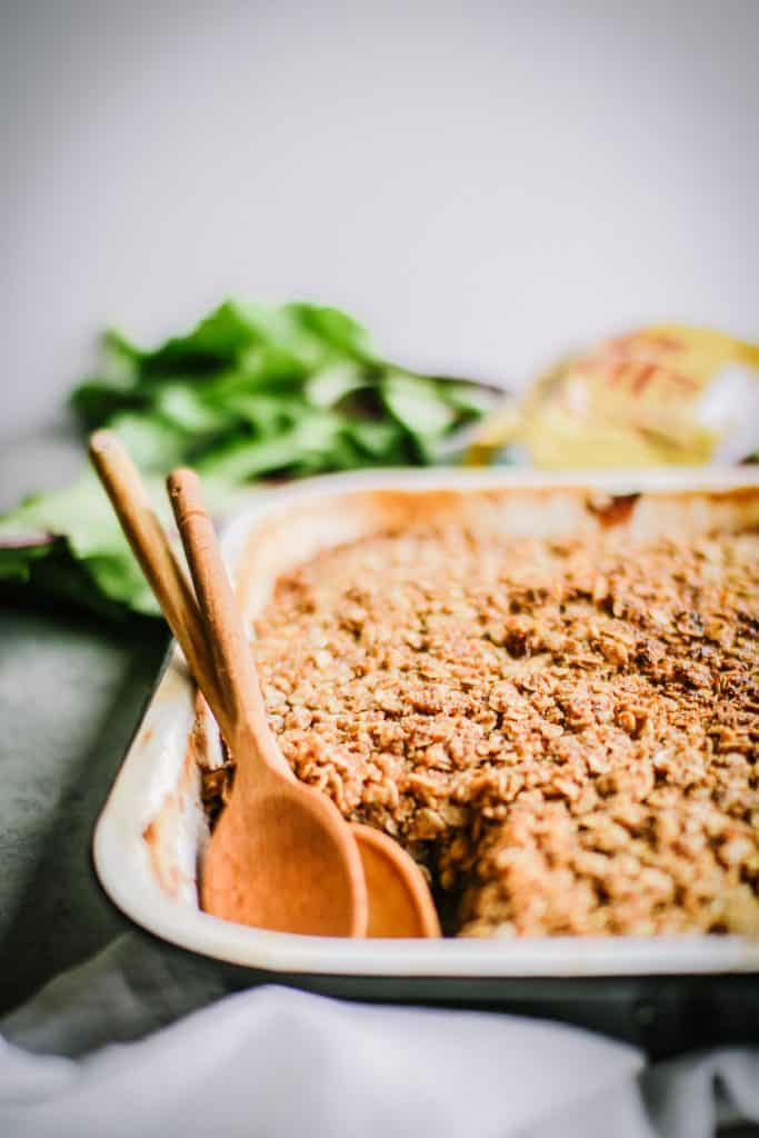 Up close image of apple crisp with two wooden spoons.