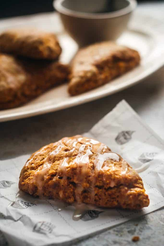 Close up of a single pumpkin scones with dripping cinnamon glaze.